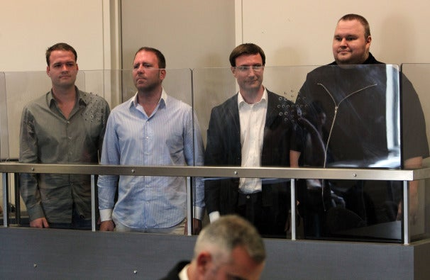 Left to right, Mathias Ortmann, Fin Batato and Bram Van der Kolk, and Kim Dotcom, in court January 20