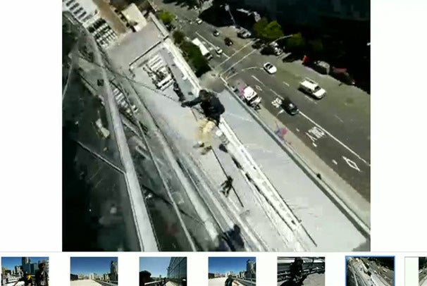 Deliverymen rappel down the side of the building