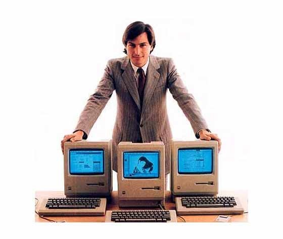Steve Jobs poses with the original Mac.